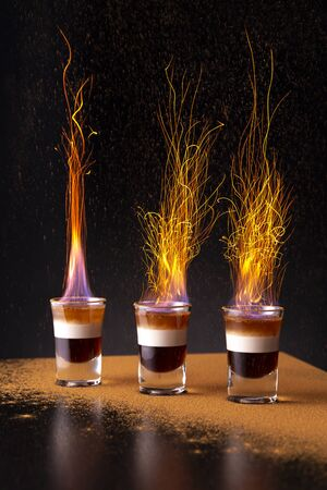 Three shots of burning B-52 cocktail placed on a bar counter, with sprinkling of cinnamon powder causing sparkes