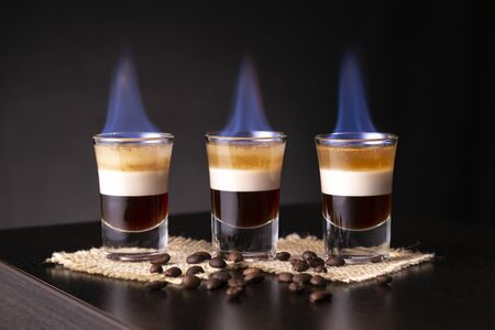 Three shots of flaming B-52 cocktail placed on a bar counter