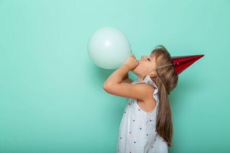 Portrait of a beautiful little girl celebrating her birthday, wearing party hat and blowing a balloon, isolated on mint colored background