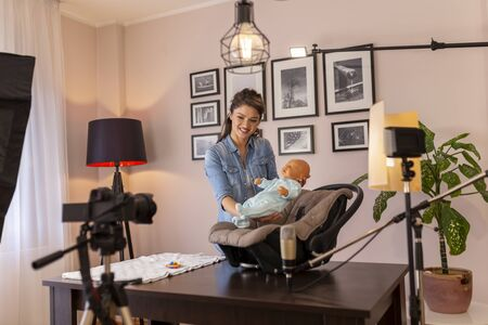 Female vlogger recording a video about newborn baby handling and positioning and the use of a car seat for safe transportation as part of online prenatal classes