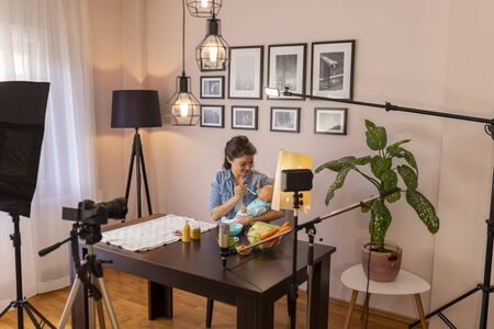 Female vlogger recording video about introducing a soft food into baby nutrition and feeding a baby as part of online prenatal classes course