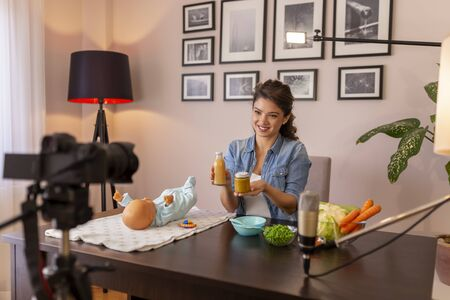 Female vlogger filming video about introducing soft food to baby nutrition and preparation of fresh fruit and vegetable porridges as part of online prenatal classes course