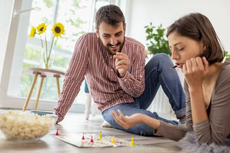 Couple in love enjoying their time together, eating popcorn and having fun while playing ludo board game