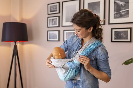 Female vlogger recording video about the use and proper wrapping of baby carrier scarfs as part of online prenatal classes course