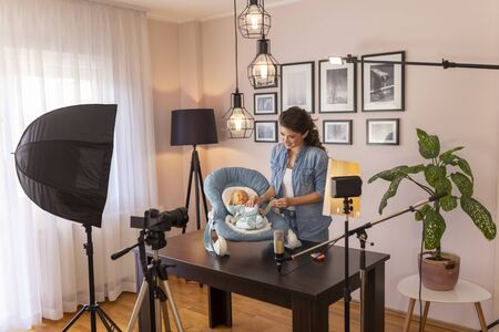 Influencer making video about the use of newborn baby portable swing for getting baby to sleep easier as part of online prenatal classes course 免版税图像