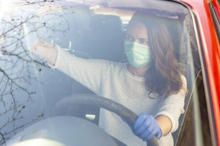 Woman wearing medical face protection mask and protective gloves, driving a car; covid-19 protection and prevention measures and safety protocols for everyday life