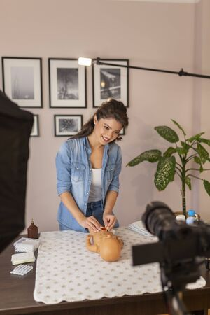 Nurse recording educational newborn baby care videos about umbilical cord care and disinfection as part of online birthing classes
