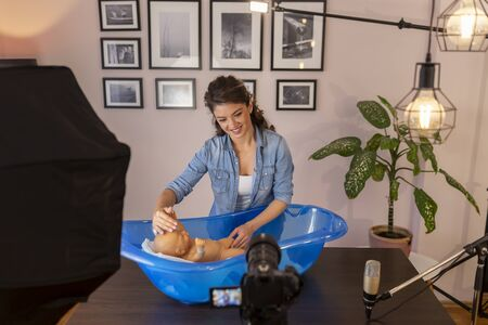 Midwife making video about newborn baby bathing as part of online birthing classes; female influencer filming tutorial about newborn baby care