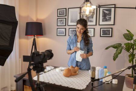 Midwife filming video about changing newborn baby diapers; female influencer making tutorial about newborn baby care as part of online birthing classes course
