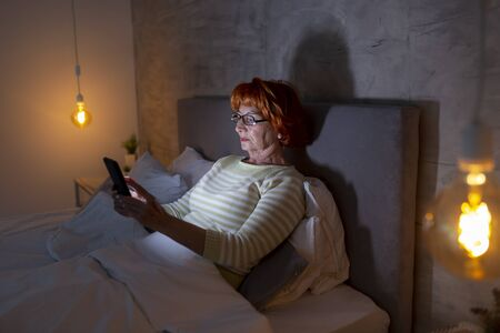 Elderly woman wearing pajamas sitting on bed, surfing the net using a smart phone Standard-Bild