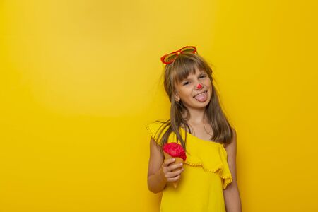 Little girl having fun while eating ice cream in a cone isolated on yellow colored background Stock Photo