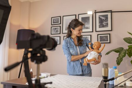 Midwife making video about double diapering and newborn baby proper hip positioning to prevent hip dysplasia as part of online birthing classes course
