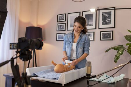 Female vlogger filming video about changing newborn baby diapers; female influencer making tutorial about newborn baby care as part of online birthing classes course 免版税图像