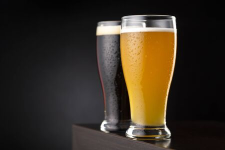 Two glasses of cold unfiltered wheat beer and dark beer placed on a bar counter with copy space