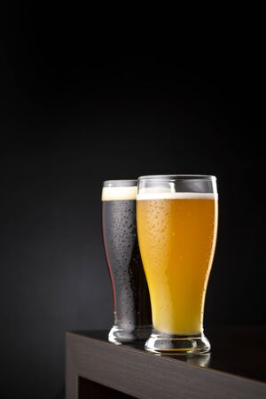 Two glasses of cold unfiltered wheat beer and dark beer placed on a bar counter with copy space Stockfoto