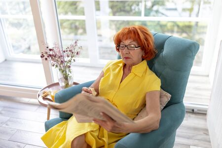 Beautiful senior woman relaxing at home, enjoying her leisure time, reading newspaper and having breakfast