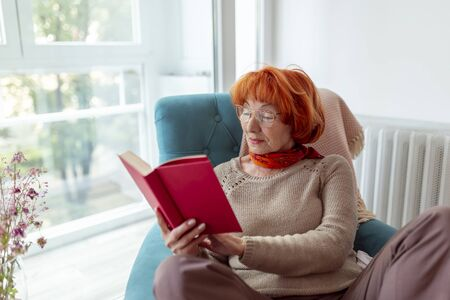 Elderly woman sitting in an armchair by the window, reading a book and enjoying her leisure time at home