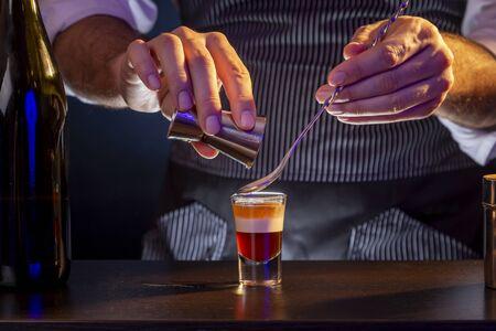Barkeeper, der einen B-52-Schichtcocktail herstellt und irische Sahne aus einem Messbecher mit einem Cocktaillöffel in ein Schnapsglas gießt
