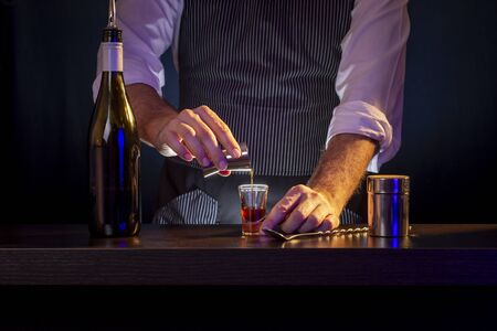 Bartender making B-52 layered cocktail, pouring coffee liqueur from measuring cup into a shot glass
