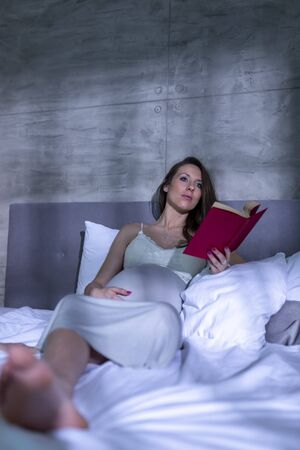 Beautiful pregnant woman wearing nightgown, lying in bed and relaxing at home at night, reading a book Banque d'images
