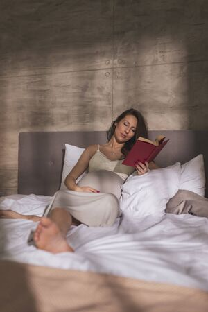 Pregnant woman wearing nightgown, lying in bed and relaxing at home in the morning, reading a book