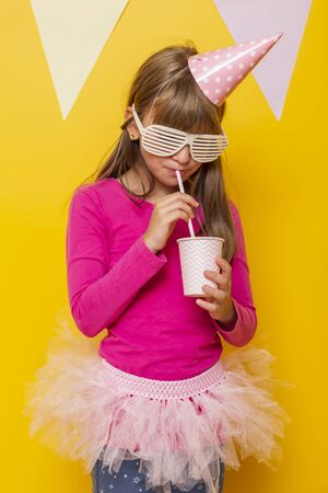Beautiful little girl wearing party glasses and birthday hat, drinking juice with a straw, isolated on yellow colored background with party flags Banco de Imagens