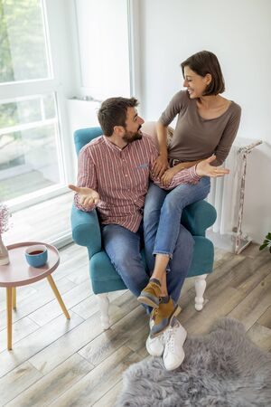 Couple in love sitting in an armchair by the window, cuddling, having fun and enjoying their time together Stock Photo