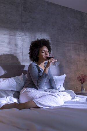 Beautiful young mixed race woman wearing pajamas sitting on the bed, drinking wine and relaxing at home at night Imagens