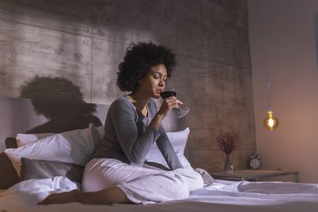 Woman wearing pajamas sitting on the bed, drinking wine and enjoying leisure time at home Imagens