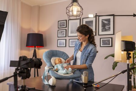 Vlogger making video about use of newborn baby swing seat as part of online birthing classes course Imagens