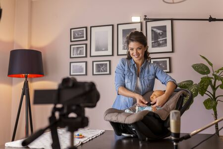 Female vlogger filming tutorial about newborn baby care, baby handling and positioning and the use of a car seat for safe transportation as part of online birthing classes Imagens