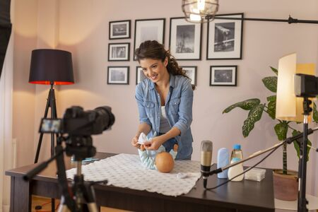 Female vlogger filming video about newborn baby scratching protection as part of online prenatal classes course; female influencer recording tutorial about newborn baby care Imagens