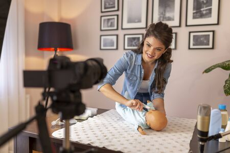 Female vlogger recording video about newborn baby oral cavity care; influencer making video about cleaning newborn baby mouth as part of online birthing classes