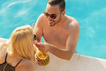 High angle view of a beautiful young couple drinking cocktails and having fun at a swimming pool