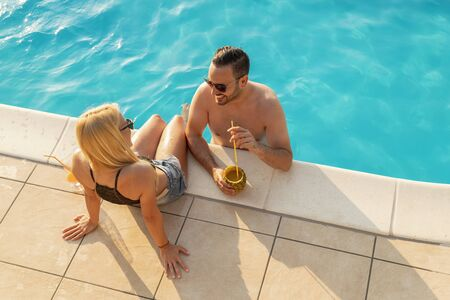 High angle view of a beautiful young couple drinking cocktails, sunbathing and having fun at a swimming pool Imagens