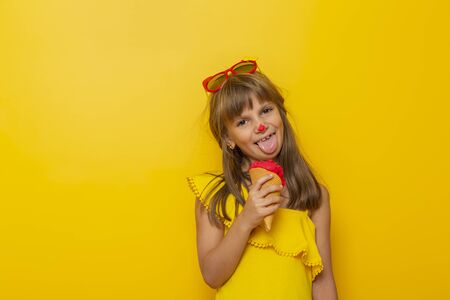 Little girl having fun while eating ice cream in a cone isolated on yellow colored background Imagens