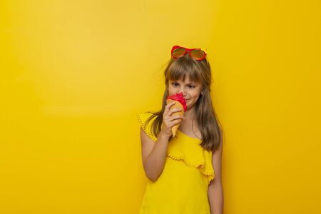 Beautiful little girl having fun and making funny faces while eating an ice cream in a cone isolated on yellow colored background