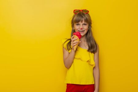 Beautiful little girl eating an ice cream in a cone isolated on yellow colored background Imagens