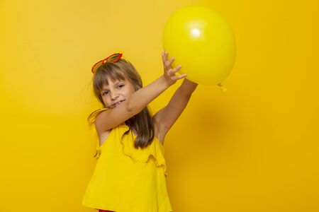 Little girl having fun while playing with a yellow balloon isolated on yellow colored background