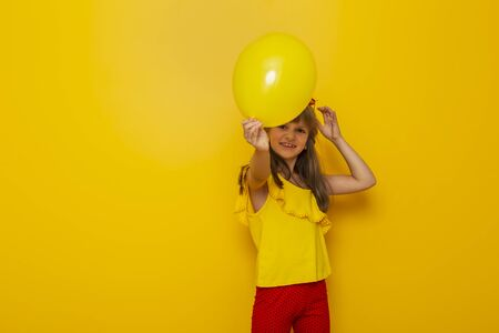 Child having fun while playing with a yellow balloon isolated on yellow colored background
