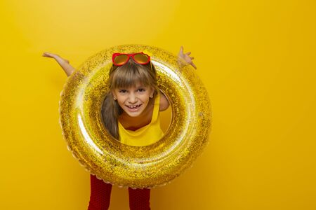 Little girl playing with an inflatable swim ring, getting ready for beach summer vacation, isolated on yellow colored background Imagens