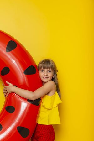 Little girl hugging an inflatable watermelon swim ring, getting ready for beach summer vacation, isolated on yellow colored background Imagens