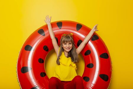 Child sitting in an inflatable watermelon shaped swim ring, daydreaming about beach summer vacations, isolated on yellow colored background