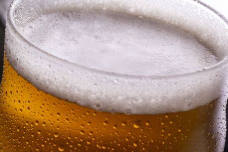 Close up of glass of cold beer with dew and condensate water droplets on the surface of the glass