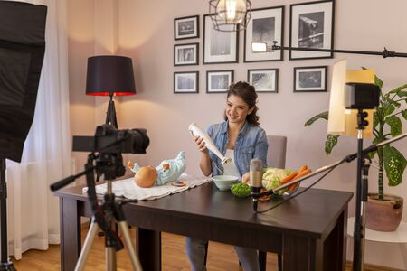 Vlogger filming video about introducing soft food to baby nutrition and preparation of fresh fruit and vegetable porridges using stick mixer as part of online birthing classes course