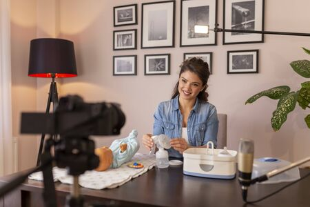 Healthcare specialist filming video about baby bottles sterilizing with help of electric steam sterilizer as part of online birthing classes course