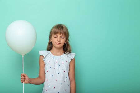 Beautiful little girl holding a balloon with eyes closed, making a wish, isolated on mint colored background with copy space