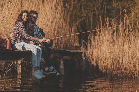 Couple in love sitting at lake docks, fishing and enjoying a beautiful sunny autumn day in nature