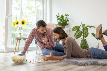 Couple in love enjoying their time together, eating popcorn and having fun while playing ludo board game Stock Photo
