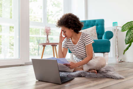 Beautiful young mixed race woman sitting on the living room floor, calculating bank loan payout rates and paying household bills, anxious and worried